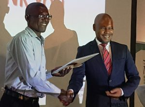 Innovation Competition First place Winner receiving his certificate from Mr Tlhoaele, Chairperson of the Finance and Investment Committee